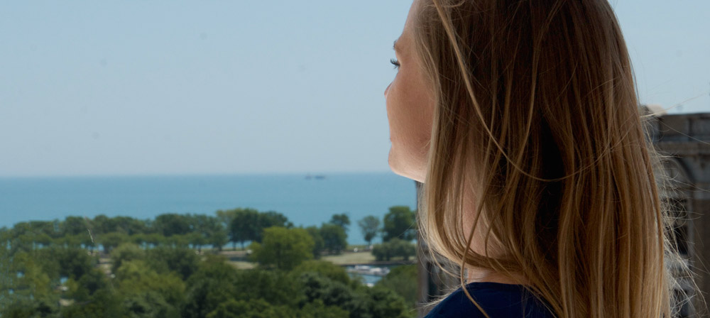 Woman taking in the view of Lincoln Park and Lake Michigan from the roofdeck