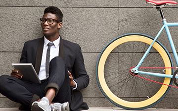 A well dressed man sitting next to a colorful bike