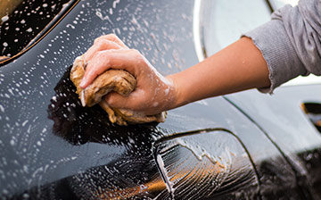 A close up of a person wiping down a car with a soapy sponge