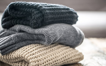 A stack of neatly folded chunky knit sweaters
