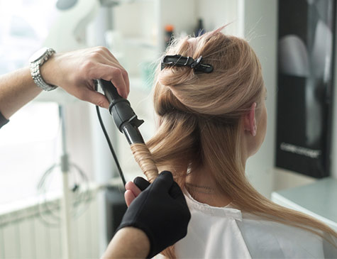 Woman having her hair curled at a salon